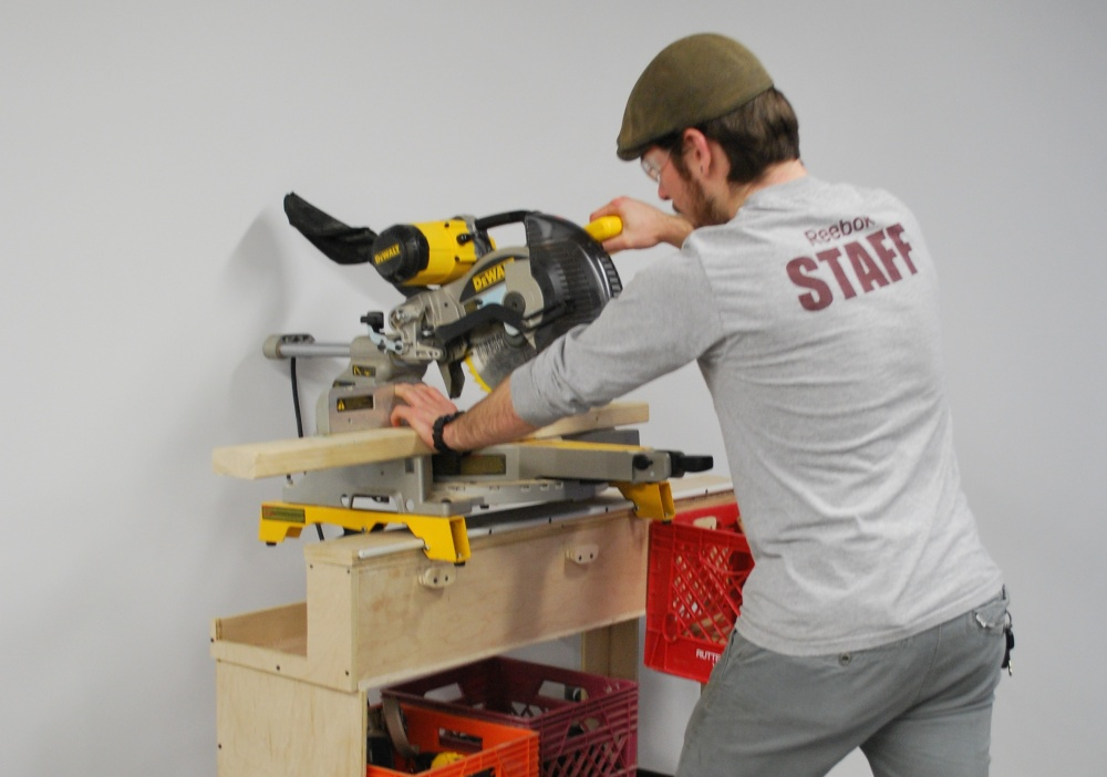 The rail along the top of the cart fits the mounting brackets of a Dewalt miter saw for transportation and use.