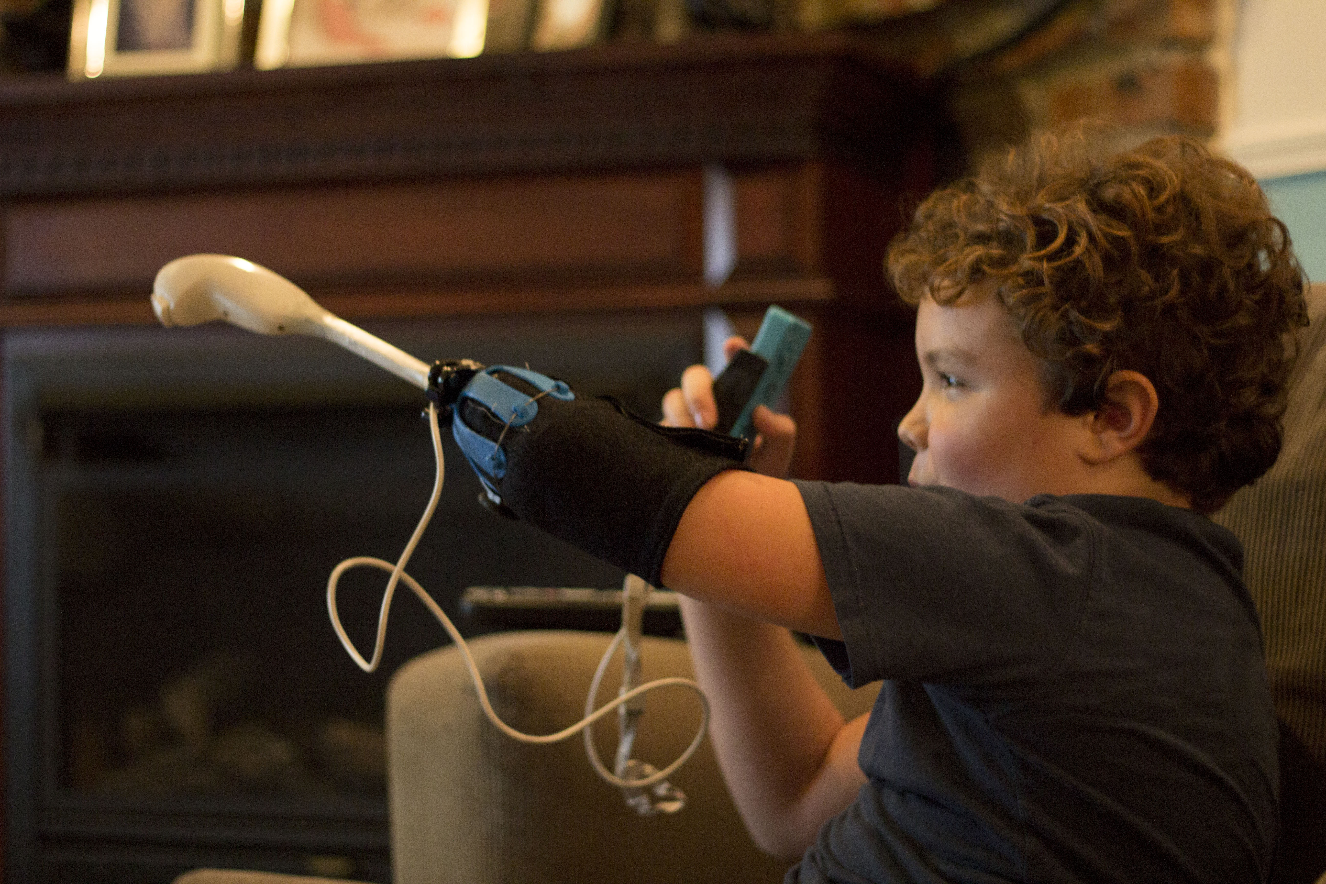 The Nintendo Wii uses a two handed interface. This attachment allows Aidan to use both of the Wii controllers simultaneously.